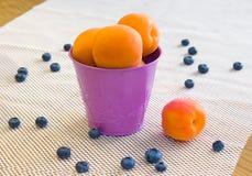Aprikosen in einem violetten Eimer und in den Blaubeeren auf einem weißen backgroun Lizenzfreie Stockfotografie