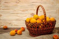 Aprikosen in einem Weidenkorb auf einem hölzernen Stockfotos