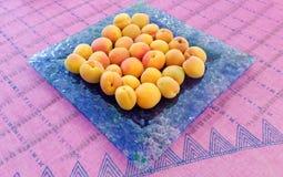 Aprikosen in einer blauen Platte Stockfotos