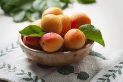 Aprikosen in einer hölzernen Schüssel Stockbilder