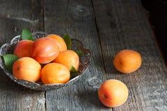 Aprikosen in einer Schüssel auf hölzernem Hintergrund Lizenzfreies Stockbild
