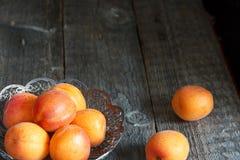Aprikosen in einer Schüssel auf hölzernem Hintergrund Stockbild
