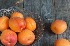 Aprikosen in einer Schüssel auf hölzernem Hintergrund Lizenzfreies Stockfoto