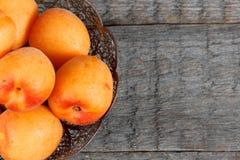 Aprikosen in einer Schüssel auf hölzernem Hintergrund Lizenzfreie Stockfotos