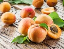 Aprikosen und sein Querschnitt auf dem alten Holz lizenzfreie stockfotografie