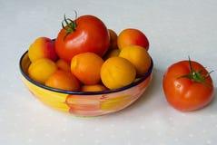 Aprikosen und Tomaten in einer Schüssel auf dem weißen Stoff Stockbilder