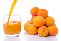 Aprikosensaft goss in ein Glas nahe einem Haufen von Aprikosen Lizenzfreie Stockbilder
