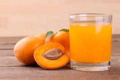 Aprikosfruktsaft bredvid nya aprikors på en brun träbakgrund Royaltyfri Foto
