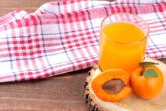 Aprikosfruktsaft bredvid nya aprikors på en brun träbakgrund Royaltyfri Bild