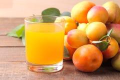 Aprikosfruktsaft bredvid nya aprikors på en brun träbakgrund Royaltyfria Bilder