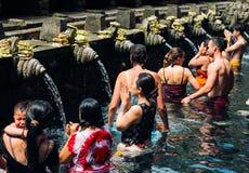 23 April, 2016, Bali, Indonesië - de vrouw bij het heilige bronwater bidt bij Pura Tirtha Empul-tempel Stock Afbeeldingen
