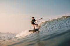 12 april, 2019 Bali, Indonesi? Tribune op de rit van de Peddelsurfer op oceaangolf Tribune op Peddel die bij golven in Bali surfe royalty-vrije stock fotografie