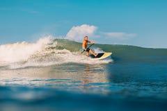 12 april, 2019 Bali, Indonesi? Tribune op de rit van de Peddelsurfer op oceaangolf Tribune op Peddel die bij golven in Bali surfe stock foto's