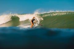 12 april, 2019 Bali, Indonesi? Tribune op de rit van de Peddelsurfer op oceaangolf Tribune op Peddel die bij golven in Bali surfe stock afbeelding