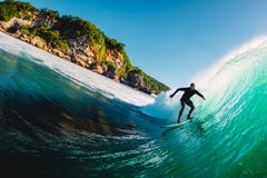 April 18, 2019. Bali, Indonesia. Surfer ride on barrel wave. Professional surfing at big waves in Padang Padang royalty free stock images