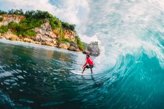April 18, 2019. Bali, Indonesia. Surfer ride on barrel wave. Professional surfing at big waves in Padang Padang royalty free stock image