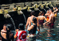 23 April, 2016, Bali, Indonesia - woman at the holy spring water is praying at Pura Tirtha Empul temple. During religious ceremony in Tampak Siring, Bali stock images