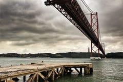 25. April Bridge in Lissabon an einem bewölkten Tag Lizenzfreies Stockfoto