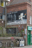 April 2014 - Bristol, United Kingdom: A graffiti of Banksy. Called The Mild Mild West, of a bear with fire in his hand aiming at three police officers. The Mild Stock Photo