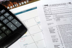 April Calendar and Tax Return. This is a close up image of a tax return, April calendar, and calculator royalty free stock photo