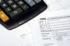 April Calendar and Tax Return. This is a close up image of a tax return, April calendar, and calculator royalty free stock photography