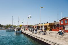 April 17, 2014. The city of nynashamn in Sweden. The embankment of the Baltic Sea. People are resting sitting on a wooden dock nea royalty free stock photography
