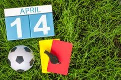14 april Dag 14 van maand, kalender op achtergrond van het voetbal de groene gras met voetbaluitrusting De de lentetijd… nam blad Royalty-vrije Stock Foto