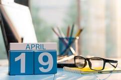 19 april Dag 19 van maand, kalender op bedrijfsbureauachtergrond, werkplaats met laptop en glazen De de lentetijd… nam bladeren,  Stock Afbeelding
