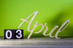 3 april Dag 3 van maand, kalender op houten lijst en groene achtergrond De lentetijd, lege ruimte voor tekst Stock Foto