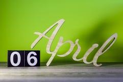6 april Dag 6 van maand, kalender op houten lijst en groene achtergrond De lentetijd, lege ruimte voor tekst Stock Foto's