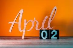 2 april Dag 2 van april-maand, kalender op houten lijst en oranje achtergrond De de lentetijd… nam bladeren, natuurlijke achtergr Stock Afbeelding