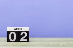 2 april Dag 2 van maand, kalender op houten lijst en purpere achtergrond De lentetijd, lege ruimte voor tekst Stock Foto