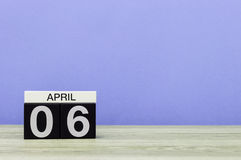 6 april Dag 6 van maand, kalender op houten lijst en purpere achtergrond De lentetijd, lege ruimte voor tekst Stock Foto