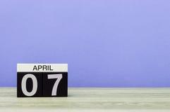 7 april Dag 7 van maand, kalender op houten lijst en purpere achtergrond De lentetijd, lege ruimte voor tekst Stock Foto's