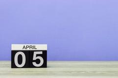 5 april Dag 5 van maand, kalender op houten lijst en purpere achtergrond De lentetijd, lege ruimte voor tekst Stock Afbeelding