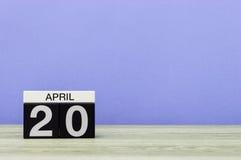20 april Dag 20 van maand, kalender op houten lijst en purpere achtergrond De lentetijd, lege ruimte voor tekst Royalty-vrije Stock Foto