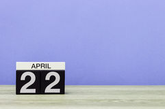 22 april Dag 22 van maand, kalender op houten lijst en purpere achtergrond De lentetijd, lege ruimte voor tekst Royalty-vrije Stock Afbeeldingen