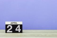 24 april Dag 24 van maand, kalender op houten lijst en purpere achtergrond De lentetijd, lege ruimte voor tekst Stock Fotografie