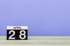 28 april Dag 28 van maand, kalender op houten lijst en purpere achtergrond De lentetijd, lege ruimte voor tekst Royalty-vrije Stock Foto