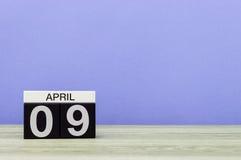 9 april Dag 9 van maand, kalender op houten lijst en purpere achtergrond De lentetijd, lege ruimte voor tekst Royalty-vrije Stock Afbeelding