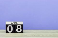 8 april Dag 8 van maand, kalender op houten lijst en purpere achtergrond De lentetijd, lege ruimte voor tekst Royalty-vrije Stock Foto