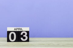 3 april Dag 3 van maand, kalender op houten lijst en purpere achtergrond De lentetijd, lege ruimte voor tekst Royalty-vrije Stock Fotografie
