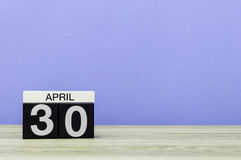 30 april Dag 30 van maand, kalender op houten lijst en purpere achtergrond De lentetijd, lege ruimte voor tekst Royalty-vrije Stock Foto