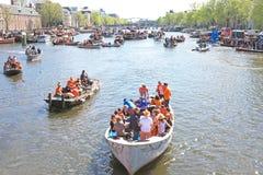 27 APRIL: De kanalenhoogtepunt van Amsterdam van boten en mensen in oranje du Stock Fotografie