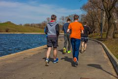 19 April, 2018 - de stadspark van Moskou Een groep jongeren die in sportkleding lopen royalty-vrije stock afbeelding
