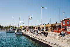 17. April 2014 Die Stadt von nynashamn in Schweden Der Damm der Ostsee Leute stehen das Sitzen auf einem hölzernen Dock nea still Lizenzfreie Stockfotografie