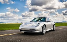 April 2, 2018 Eugene Oregon - A silver Porsche 911 sits in an em. April 2, 2018 Eugene Oregon - A silver Porsche 911 body style 996 sits on an empty road under a Stock Photo