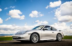 April 2, 2018 Eugene Oregon - A silver Porsche 911 sits in an empty rural road. April 2, 2018 Eugene Oregon - A silver Porsche 911 body style 996 sits on an Royalty Free Stock Photography