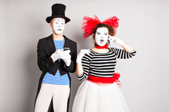 April Fool's Day concept. Couple having fun  and using a mobile phone. Royalty Free Stock Photography