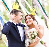 April Fools ' dag Gifta sig par som poserar med kronan, maskering Royaltyfria Bilder
